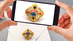Image of smartphone camera taking a photo of a gold brooch with gems