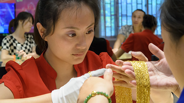 Sales associate holding gold jewelry