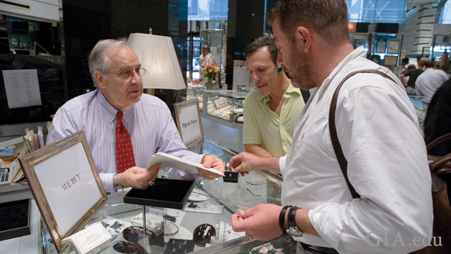 Three men look at diamond jewellery and paperwork at a jeweller's counter.