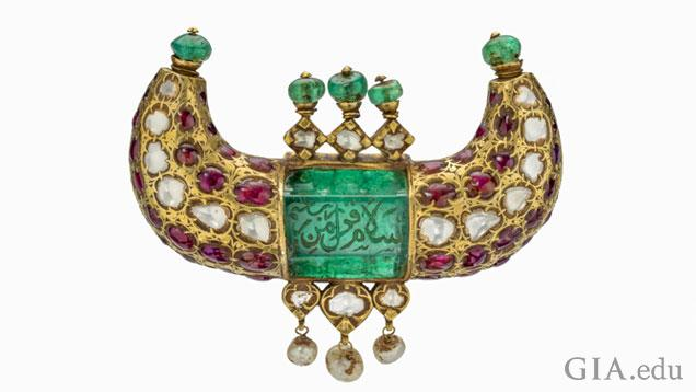This gold pendant features a 125 carat Colombian emerald engraved in Arabic with  salutations of peace. Set with diamonds, Burmese rubies, emerald beads and dangling pearls, it was made for a ruler of the Kingdom of Mysore. Mughal Era • Mysore • 18th century • emerald, ruby, diamond and pearl in 22K gold • 6 x 8.5 x 2 cm
