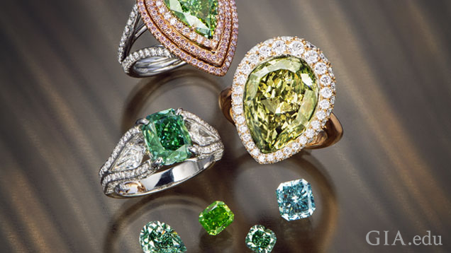 Three beautiful rings are clustered near four loose diamonds. All pieces include green diamonds of different shades.