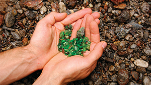 Hands holding rough tsavorite in the field