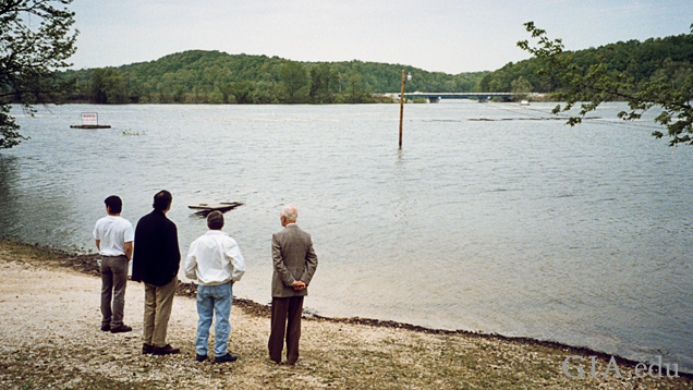 Four men on a riverbank