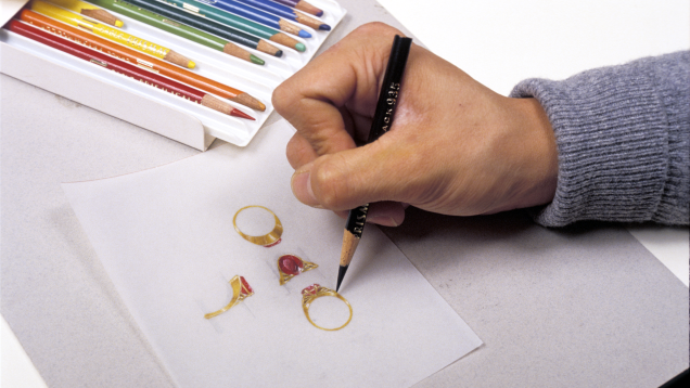 Jewelry designer using a colored pencil to draw a rendering of a ring