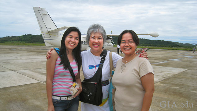 Three woman stand on a runway with a plane in the background.