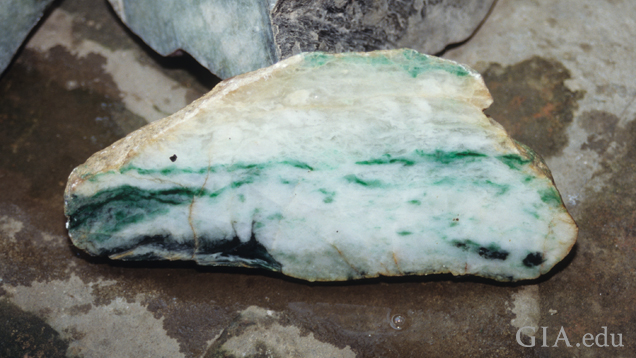 A piece of boulder shows ribbons of jade running through it.