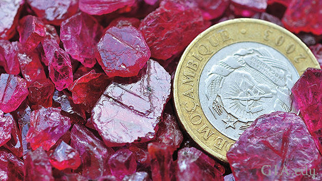A pile of rough of rubies with a coin for perspective.