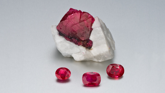 A large ruby crystal in calcite with three faceted rubies in front.