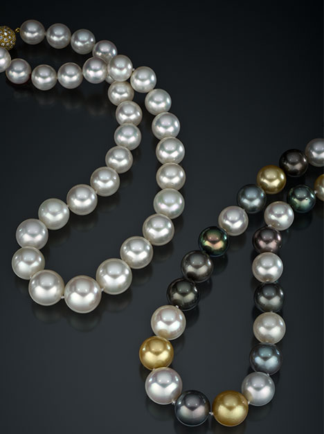 Two multi-colored South Sea cultured pearl necklaces laying next to each other on a black surface.