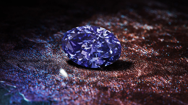 The oval-shaped Argyle Violet diamond sits on a textured brown, purple and blue surface.