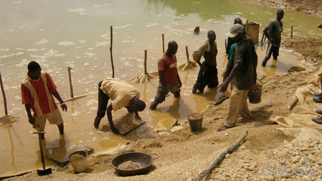 Miners, working in a row along a body of water, use hand sieves to sift gravel.
