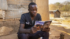 Young man reads illustrated gem guide, sitting on a cement bench.
