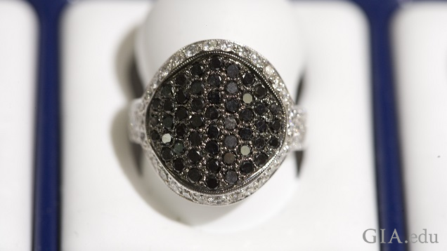 The large center of the ring is comprised of multiple black diamonds and is framed by a row of colorless diamonds.