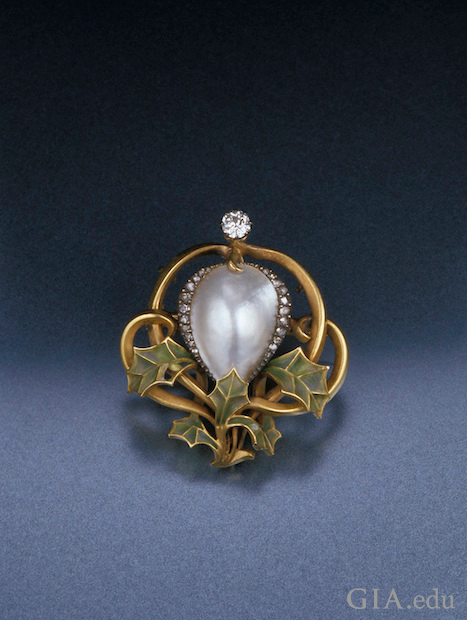 A blister pearl in the center, framed by diamonds and framed on the bottom with green enamel leaves.