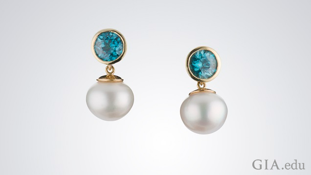 White pearls drop from round bezel set blue zircon.