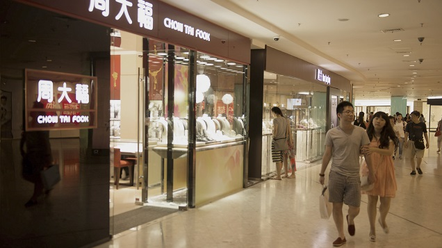 Shoppers walk in a mall past a Chow Tai Fook jewelry store.