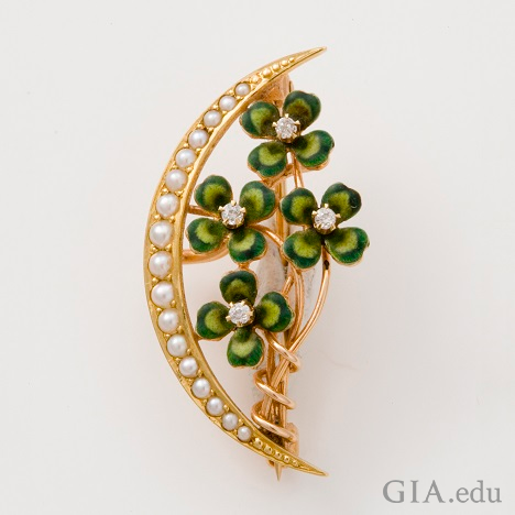 Four clover leaves climb up a branch – framed on the left side with a crescent of pearls.