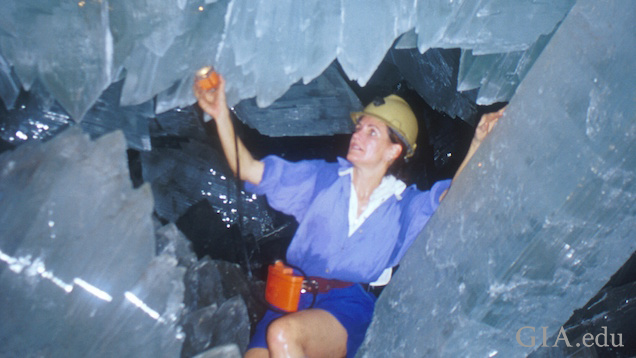 Woman shines a light on huge crystals as she crawls among them.