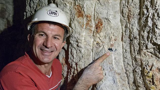 Miner points at black opal