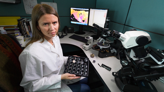 Elena Sorokina holds a tray of gem samples at her work station.