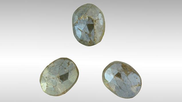 Kornerupine beads with metallic coating.