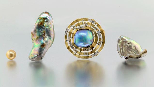 Three abalone pearls alongside South Sea bead-cultured pearl.