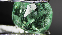Emerald with a fiber trapped by liquid resin.