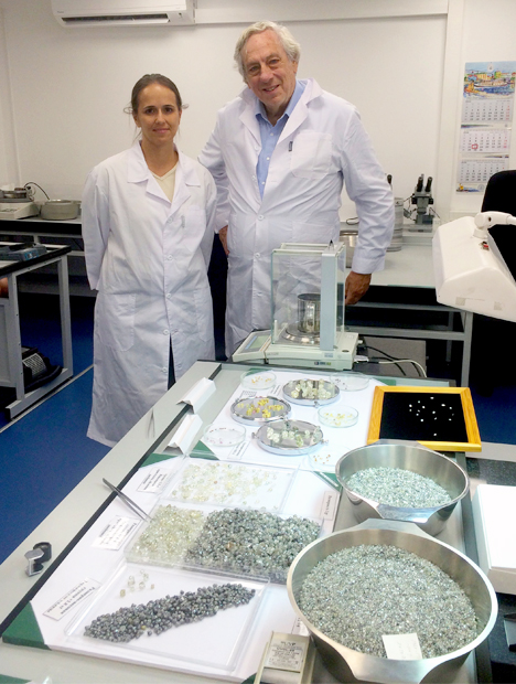 Karen Smit, left, and Russell Shor stand next to piles of diamonds in a sorting room.