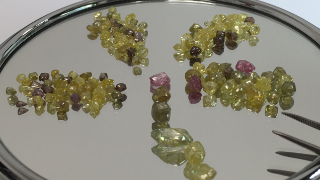 Fancy color rough diamonds are sorted into size piles on a mirror.