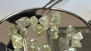 Large rough diamonds sit on a mirror.