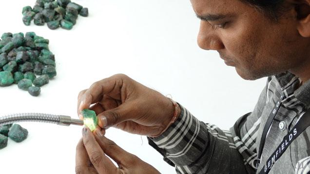 A worker uses a light to sort through several piles of rough emeralds.