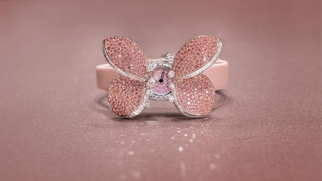 该款腕表的蝴蝶翅膀上密集地镶嵌着粉红色钻石,打开翅膀便露出了表盘, 并采用粉红色表带。