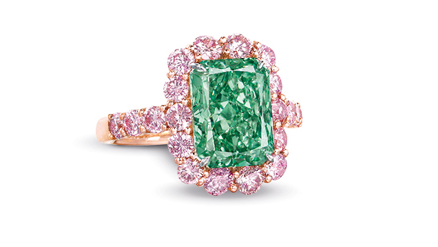 The Aurora Green Fancy Vivid green diamond is rectangle cut and mounted in a ring surrounded by Fancy pink melee diamonds.