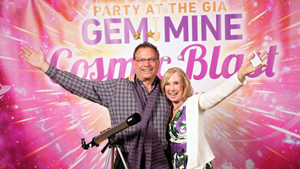 Man and woman in front of the Party at the GIA Gem Mine Cosmic Blast backdrop.