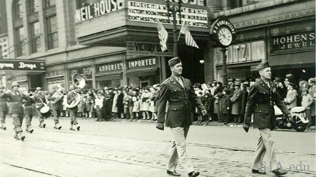 Soldiers and a band marches on a retail street.