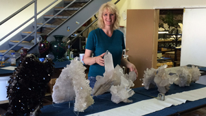 Terri Ottaway stands behind a table with several very large quartz crystal specimens are lined up on it. Some of them come up to her waist height.