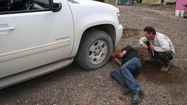 Kevin Schumacher watches as Dust Devil's Terry Clark labors to fix a flat front tire on the team's SUV.
