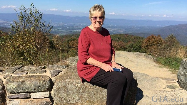 A woman sits on some rocks with a Smokey Mountain vista behind her.