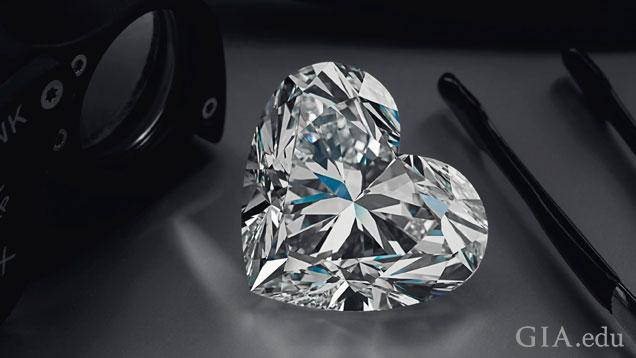 The 92 carat D flawless heart-shaped diamond is displayed next to a jeweler's loupe and tweezers.