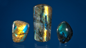 Three pieces of labradorite with yellow, blue and green flashes of color.