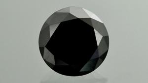 这颗重 1.04 克拉的黑色半金属圆形明亮式宝石看起来像钻石,经鉴定为碳化硼。 摄影:G. Choudhary
