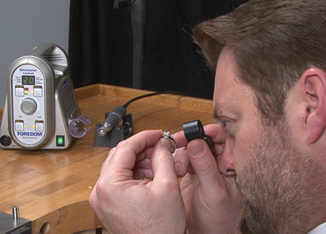 Jeweller inspecting a platinum solitaire with a loupe