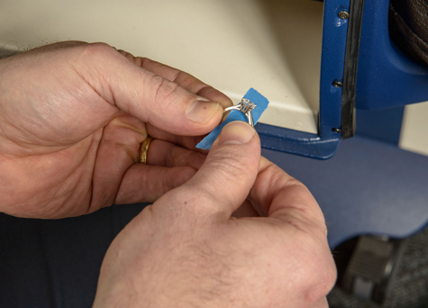 Jeweler wrapping a platinum solitaire using masking tape