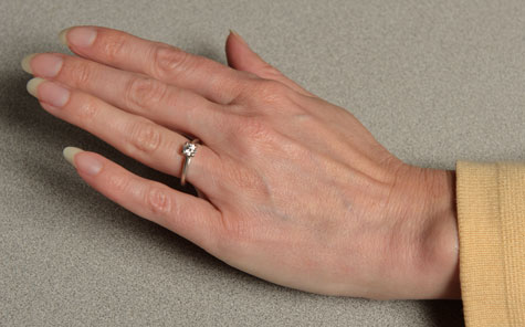 Female hand featuring a properly fitted platinum solitaire