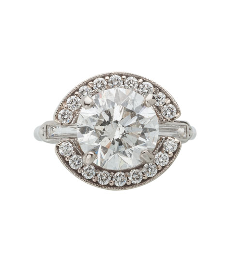 Top view of a platinum solitaire ring containing a round brilliant center diamond and baguette side diamonds. A white gold halo set with small round