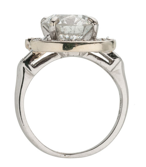 Side view of a platinum ring with a white gold and diamond halo surrounding the centre stone
