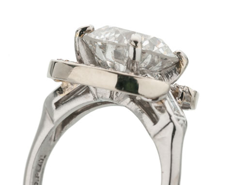 Side view of a platinum solitaire ring set with a round brilliant center diamond featuring prongs that have been repaired using white gold solder.