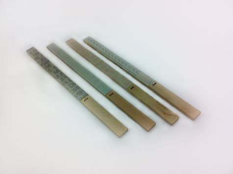 Four abrasive sticks containing micro-finishing film in four different abrasive grits.