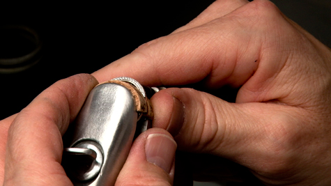 Close up of a jeweler holding a ring clamp