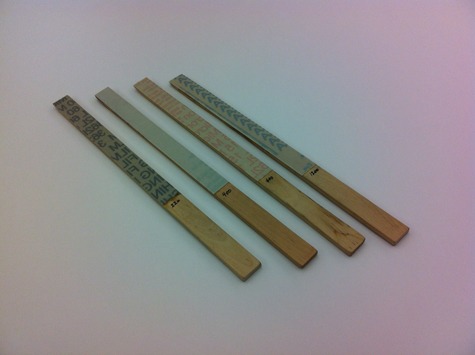 Four pieces of micro-finishing film wrapped around sanding sticks